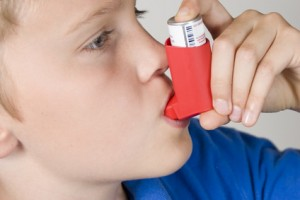 Asthma inhaler being used by boy in blue shirt
